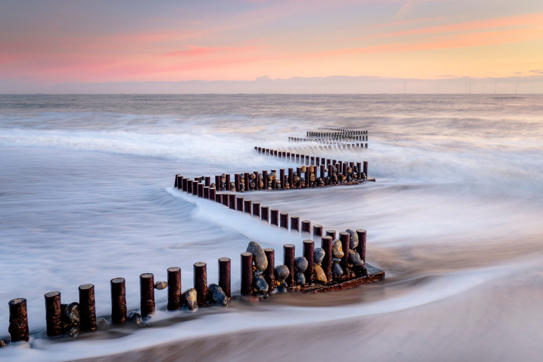 Misty beach with a trail of stones and wooden posts