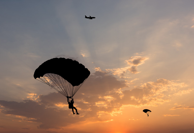 Parachutes against a golden sky