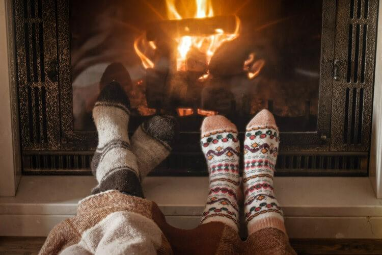 Couple in cosy socks by the fire