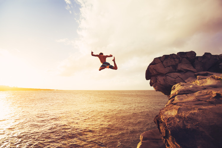 man jumping from rock into sea