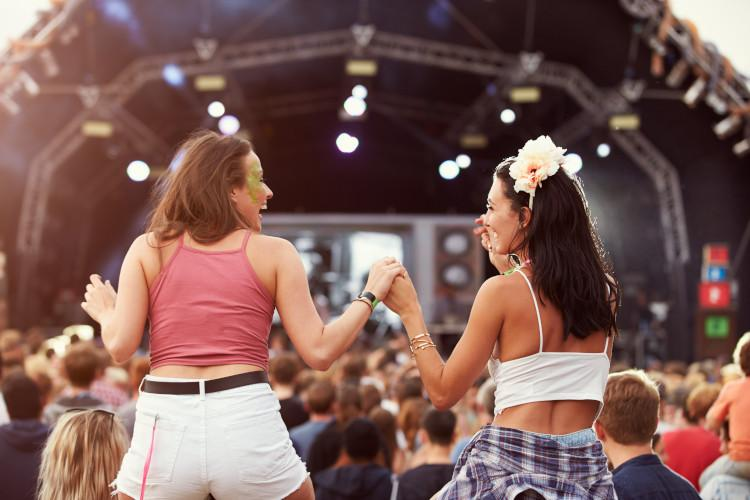 girls on shoulders at music festival