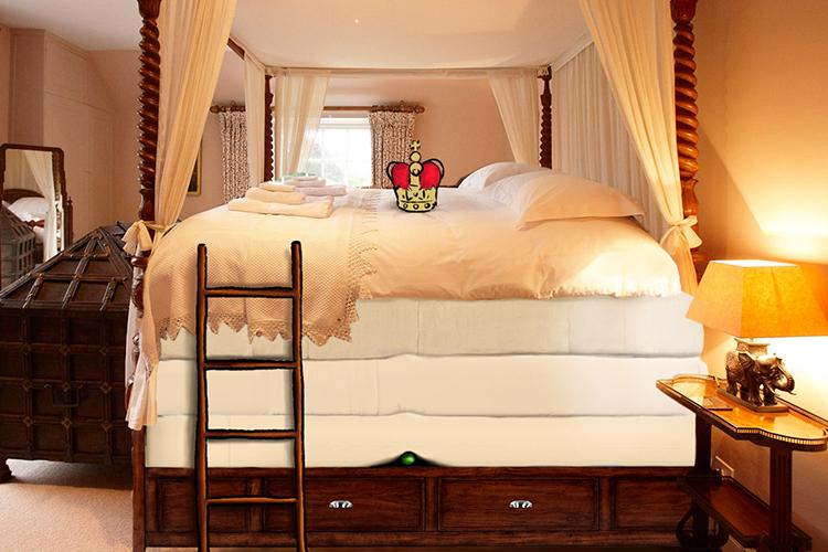 A bed at Felin Newydd House, Hay-on-Wye with a pea and crown