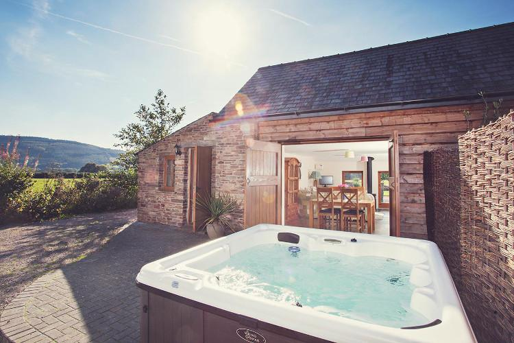 Relax in the hot tub in this luxury cottage in Wales