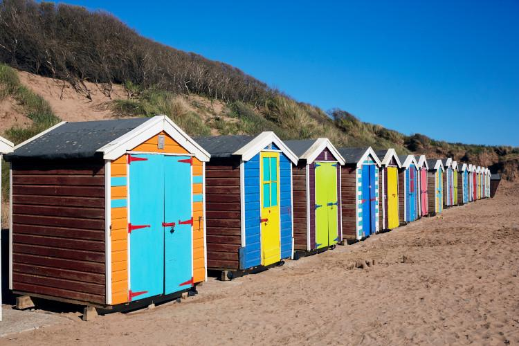line of colourful beach huts on Devon beach