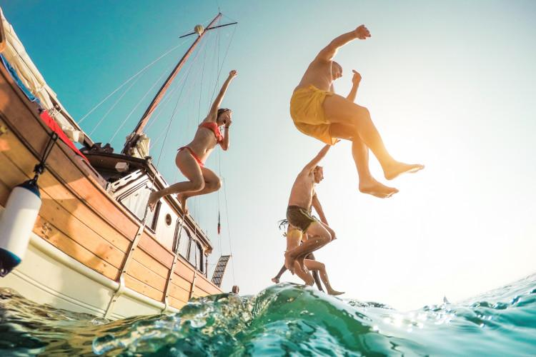 Children jumping into sea from boat