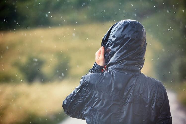 Man wearing dark waterproof jacket in the rain