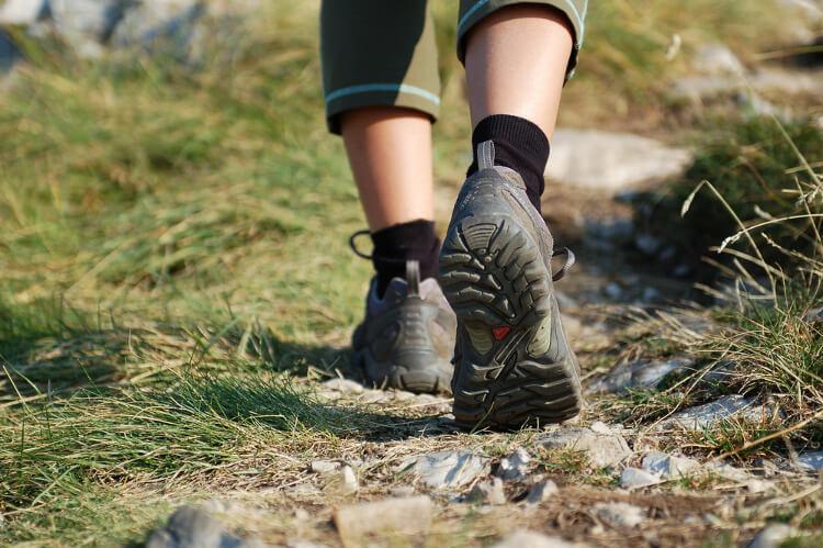 Women wearing walking shoes hiking on a trail