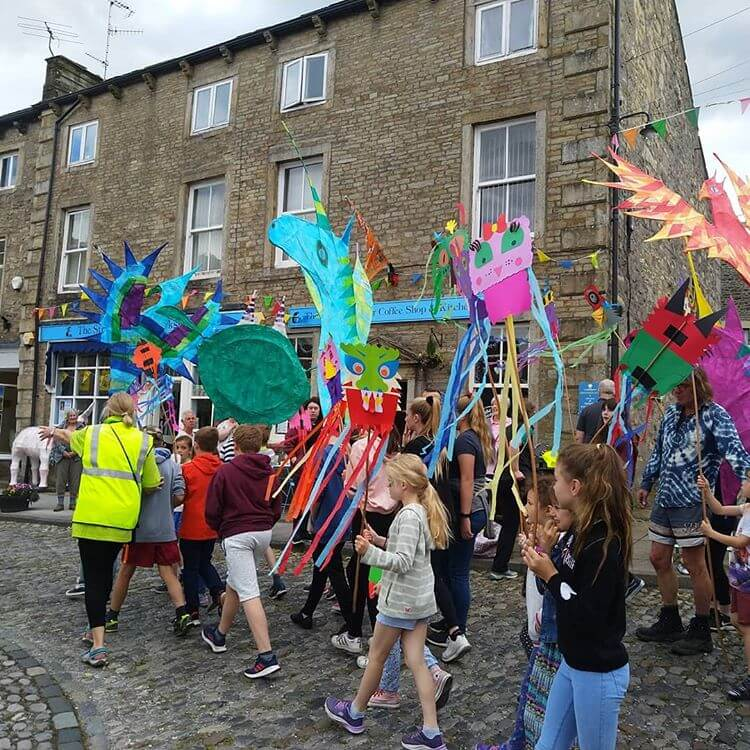 Children walking in a carnvial procession through the streets at the Grassington Festival