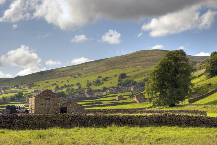 The rural countryside landscape of Swaledale in the Yorkshire Dales, with a farm shed in the foreground