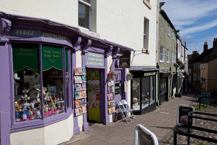 Shopping street in Richmond lined with independent shops including a fudge and chocolate shop